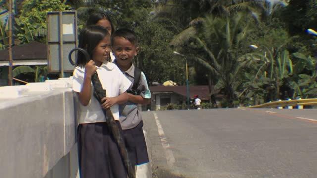 vidéos et rushes de ms young school kids walking on road / victoria, mindoro, philippines - cartable