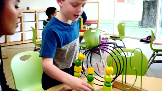 young schoolboy plays with bead maze during play therapy session - bead stock videos & royalty-free footage