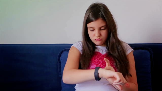 Young schoolgirl using smart watch at home