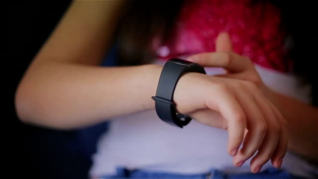 Young schoolgirl using smart watch at home,close up