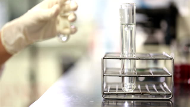 young scientist in medical laboratory estimate chemicals in tube - compound interest stock videos and b-roll footage