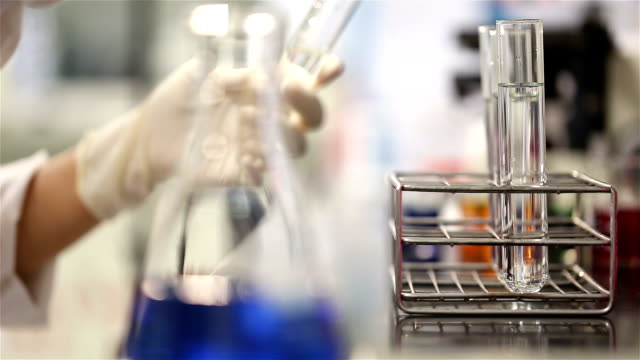 Young scientist in medical laboratory estimate chemicals in tube