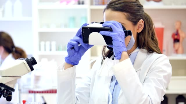 Young scientist uses virtual reality headset while conducting research