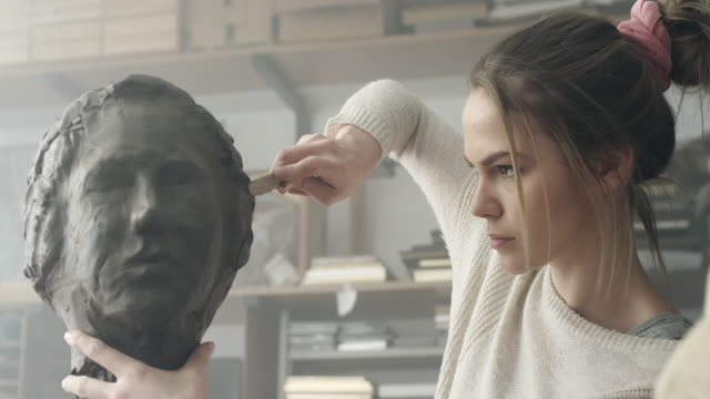 Young sculptor creates a clay sculpture