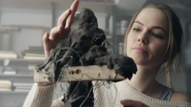junge bildhauer schafft eine tonskulptur - lehm mineral stock-videos und b-roll-filmmaterial