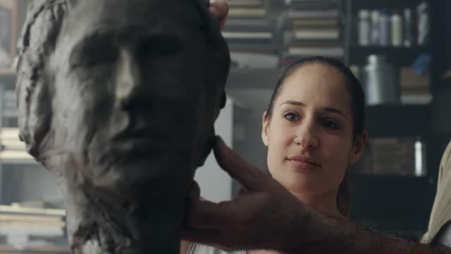 vidéos et rushes de jeune sculpteur crée une sculpture en argile - sculpture production artistique