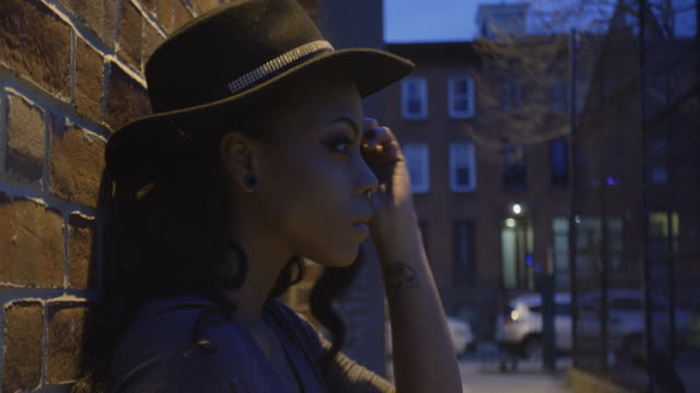 a young, sexy, black woman poses at night in the streets of brooklyn, nyc - 4k - 10 sekunden oder länger stock-videos und b-roll-filmmaterial