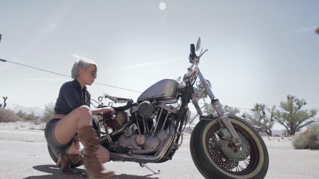 ms young sexy blond woman in hot pants walking around  bike and repairing classic motorcycle / palmdale, ca, united states   - palmdale stock videos and b-roll footage