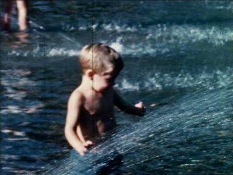 vídeos y material grabado en eventos de stock de 1960 young shirtless boy playing in fountain / washington square park / greenwich village, nyc - 1960
