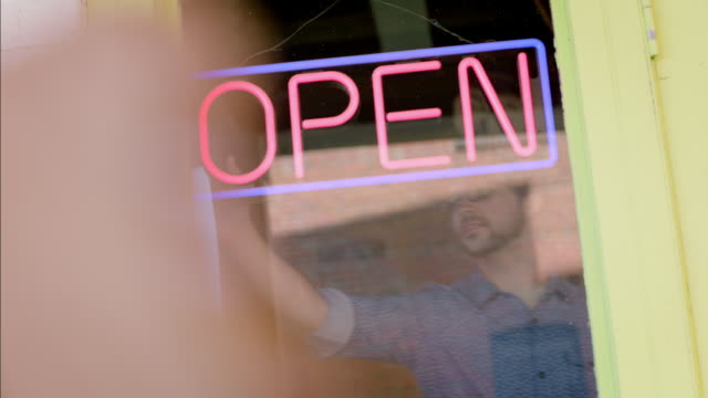 vídeos de stock, filmes e b-roll de young shop owner turns off neon open sign and closes store - fechando