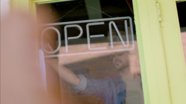 stockvideo's en b-roll-footage met young shop owner turns on neon open sign - open