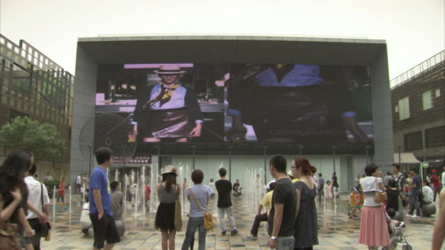vídeos de stock e filmes b-roll de young shoppers in the sanlitun shopping area of beijing watch an advertisement on a large outdoor screen, china. - billboard