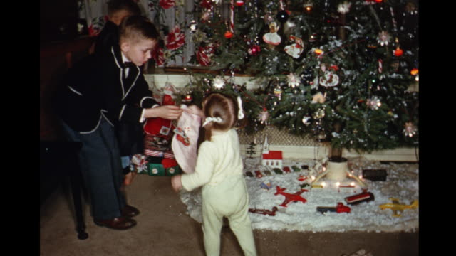 1957 HOME MOVIE Young siblings hanging stockings on Christmas tree / Toronto, Canada