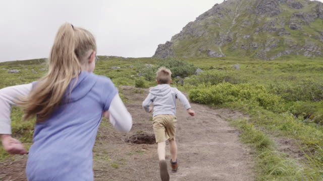 UHD 4K: Young siblings playing together and running on a trail in nature