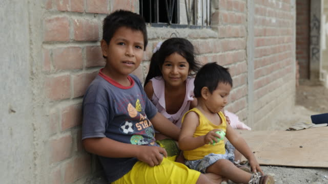 vidéos et rushes de young siblings smile to the camera while leaning at a bricked house wall - péruvien