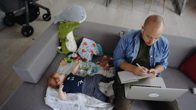 vidéos et rushes de jeune père célibataire travaillant de la maison sur un ordinateur portatif avec son fils à côté de lui - activité bancaire