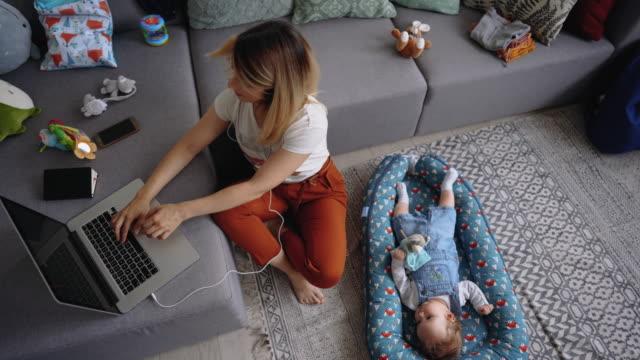 彼女の隣に横たわっている彼女の男の子と自宅で働く若いシングルマザー - 落ち着かない点の映像素材/bロール