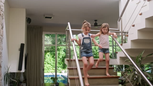 young sisters running down stairs in modern family home - moving down stock videos & royalty-free footage