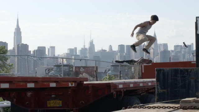 a young skateboarder crashes in slow motion - nyc - 柵点の映像素材/bロール