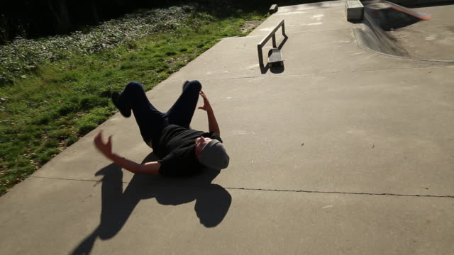 a young skateboarder doing grind tricks at a skate park. - schmerz stock-videos und b-roll-filmmaterial