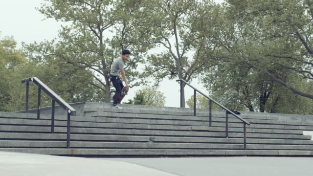 vídeos y material grabado en eventos de stock de a young skateboarder performs a trick at a queens, nyc skatepark - slow motion - 4k - manga corta