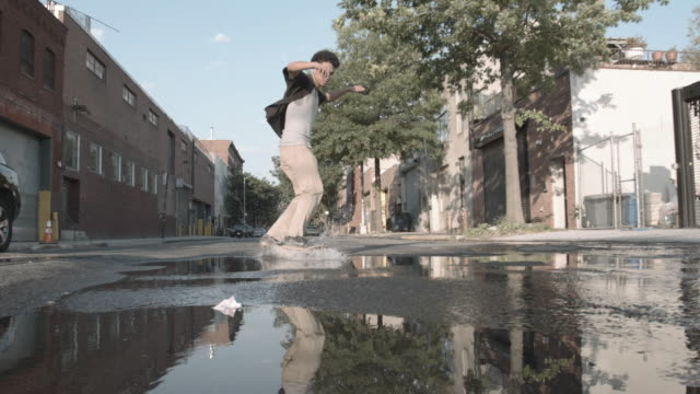 a young, skateboarder skates through a puddle in a brooklyn street in slow motion - 柵点の映像素材/bロール