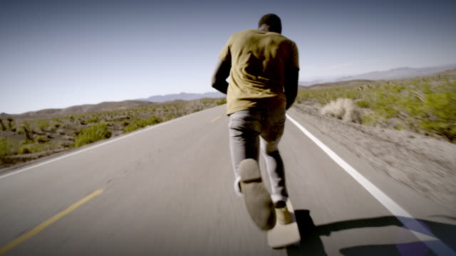 Young skater boards down a lonely desert road
