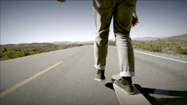 Young skater boards down a lonely desert road (slow-motion)