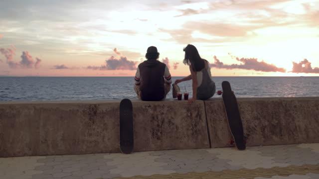 stockvideo's en b-roll-footage met jonge schaatser paar zonsondergang kijken en praten. - vriendin