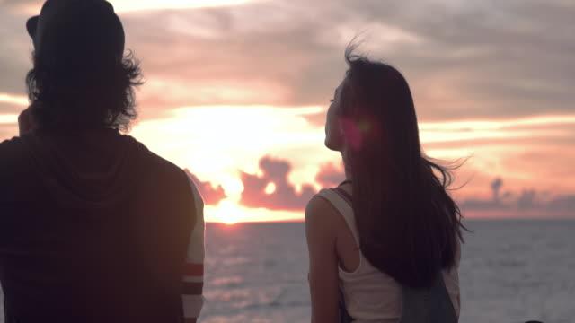 若いスケーター カップル夕日を見ていると話しています。 - couple relationship点の映像素材/bロール