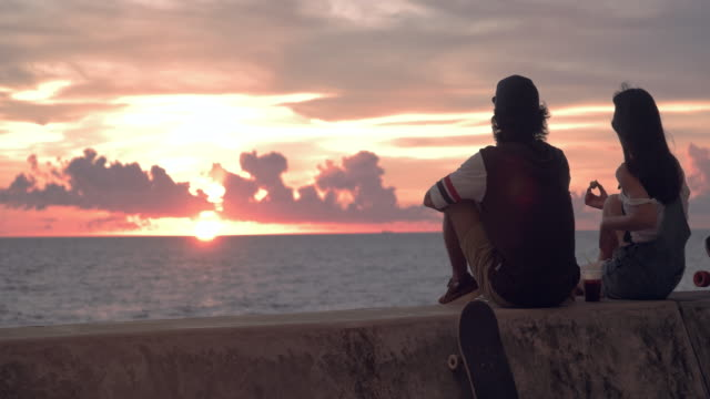 young skater couple watching sunset and talking. - longboarding stock videos & royalty-free footage