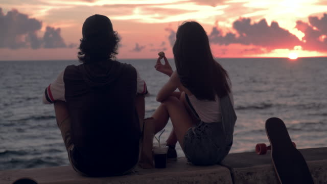 young skater couple watching sunset and talking. - japanese ethnicity stock videos & royalty-free footage