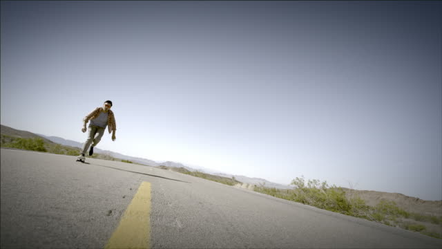 Young skater speeds up empty desert road on skateboard (slow-motion)