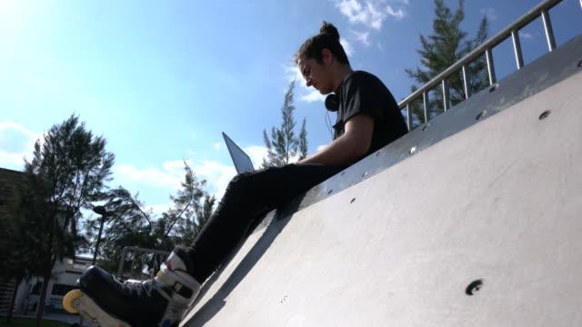 青空の下で座っている若いスケーター - 傾斜面点の映像素材/bロール