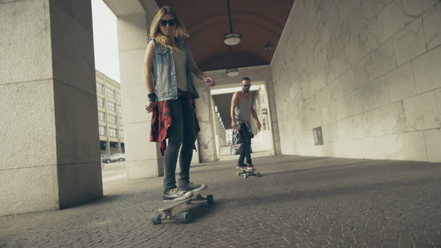 Young skaters video while riding their longboard skate