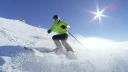 SLOW MOTION Young skier stop and smile while sprays snow in camera at ski resort