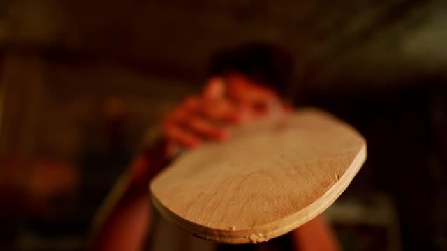 vídeos de stock, filmes e b-roll de um jovem carpinteiro habilidoso examinando um skate - lixadeira