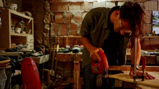 vidéos et rushes de un jeune charpentier habile utilisant un puzzle pour faire une planche à roulettes - sûreté