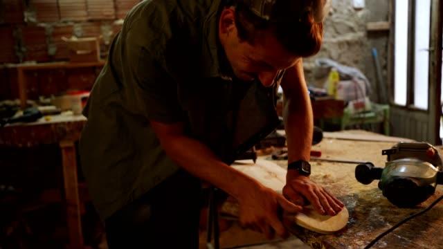 vídeos de stock, filmes e b-roll de um jovem carpinteiro habilidoso usando um papel de areia - lixadeira