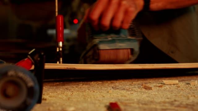 stockvideo's en b-roll-footage met een jonge bekwame timmerman die een schuurmachine gebruikt - klem