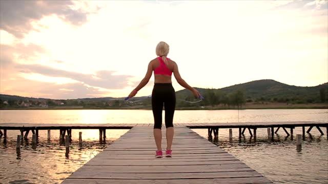 Junge schlanke Frau mit Springseil nahe dem See springen