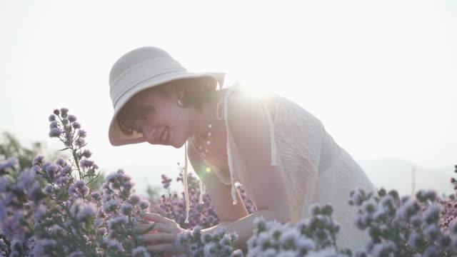 若い笑顔と笑うブルネットの女性は日没時にフラワーガーデンの匂いを楽しんでいます - 物の集まり点の映像素材/bロール