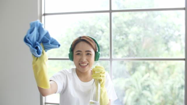 vidéos et rushes de jeune femme asiatique de lavage de jeune sourire de verre de fenêtre avec l'éponge - lessive produit d'entretien