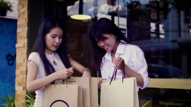 young smiling asian women shopping together and looking into shopping bags at outdoors, shopaholic friends concept - shopaholic stock videos & royalty-free footage