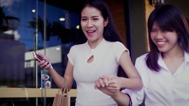 young smiling asian women shopping together with shopping bags and using a smart phone, shopaholic friends concept - shopaholic stock videos & royalty-free footage