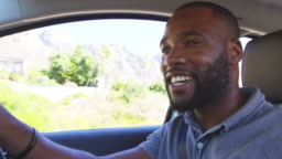 Young smiling black man driving car on a road trip
