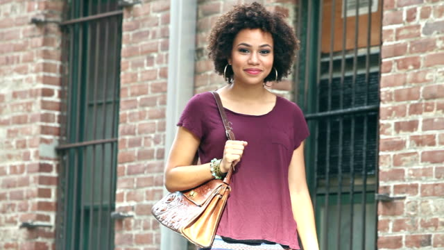young, smiling black woman walks by looking at camera - purse stock videos & royalty-free footage