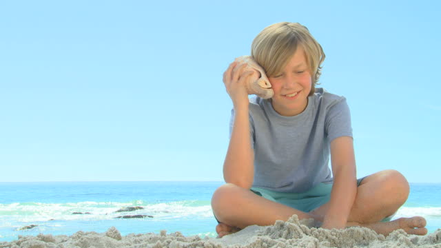young smiling boy listening to a shell / cape town, western cape, south africa - seashell stock videos and b-roll footage