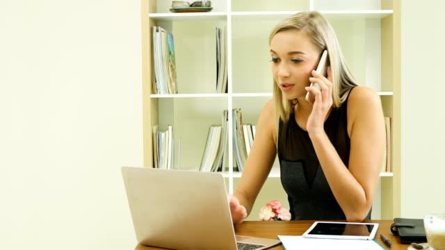 vídeos de stock, filmes e b-roll de jovem mulher de negócios sorridente usando telefone inteligente e trabalhando no escritório - smart
