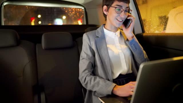 vídeos y material grabado en eventos de stock de joven empresaria sonriente conduciendo en el asiento trasero de un coche y hablando por teléfono por la noche - asiento de atrás
